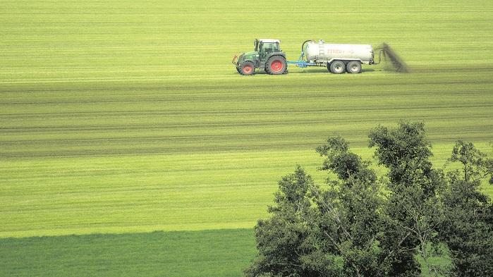 Трактор с удобрениями в цистерне удобряет почву